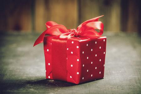 Valentines Day concept. Gift with red bow on the wooden background Valentines gift box tied with a red satin ribbon bow on rustic background.