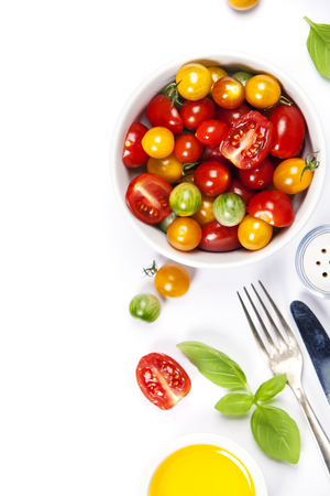 Tomato salad with fresh tomatoes, basil and olive oil on white background with copyspace