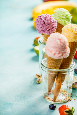 Various of ice cream flavor in cones pink (strawberry, raspberry), purple (blueberry), green (pistachio, green tea, lime) and yellow (mango, banana) setup on blue wooden background . Summer and Sweet menu concept. Reklamní fotografie