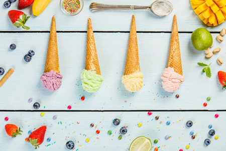 Various of ice cream flavor in cones pink(strawberry, raspberry), purple (blueberry), green (pistachio, green tea, lime) and yellow (mango, banana) setup on blue wooden background . Summer and Sweet menu concept flat lay. Reklamní fotografie