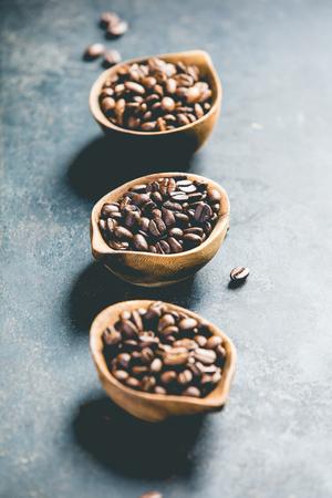 Coffee composition on dark background. Three different varieties of coffee beans on dark vintage background