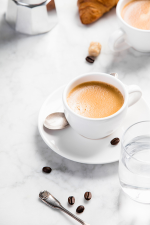 Coffee composition on white marble background. Coffee espresso in white cups with water and croissants. Breakfast concept
