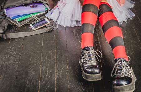 スクールバッグ、スマートフォン、サングラス、ヘッドフォンで黒い床に座っている若い代替女の子。教育、代替ライフスタイル、現代生活コンセ 写真素材