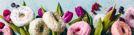Sweet and colourful doughnuts with sprinkles, purple tulips and berries falling or flying in motion against blue pastel background. Border with space for text Reklamní fotografie