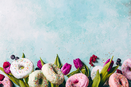 Sweet and colourful doughnuts with sprinkles, purple tulips and berries falling or flying in motion against blue pastel background