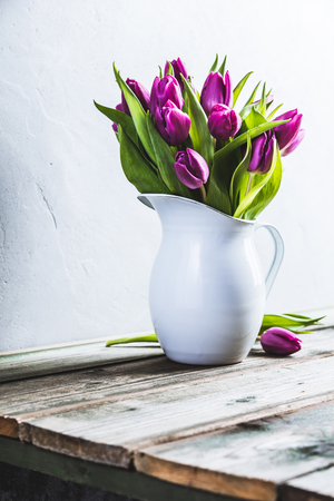 A bouquet of purple tulips in a vase against the wall