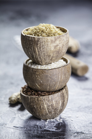 Assortment of different rice in bowls: Rice berry, Brown rice and Risotto rice on grey stone background. Foto de archivo - 97684298