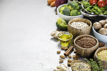 Health food concept with legumes, grains, seeds and organic vegetables on grey concrete background, Copyspace