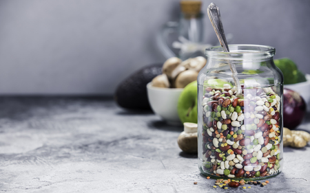 Legumes - lentils chickpeas beans green peas in a glass jar and raw vegetables. Vegan protein source. Vegetarian and healthy food concept Foto de archivo