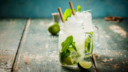Mojito cocktail with lime and mint in glass jars on the table. Copy space