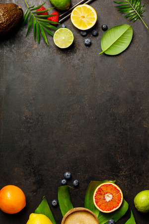 Cocktail making bar tools, tropical fruits and leaves on a dark background. Top view Stock Photo