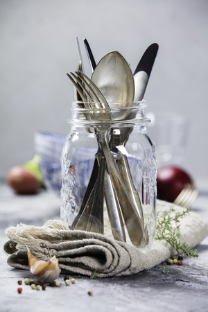 Forks spoons and knifes in a glass jar and fresh raw vegetables on grey vintage background