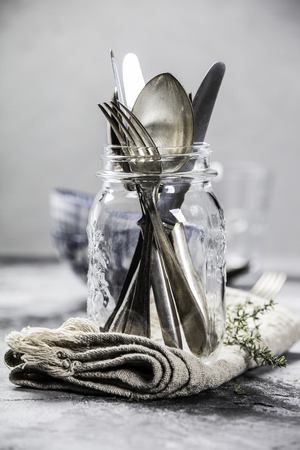 Forks spoons and knifes in a glass jar on grey vintage background