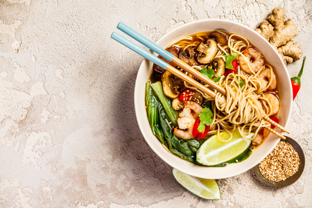 Asian soup with noodles (ramen), with miso paste, soy sauce, greens, mushrooms and shrimps prawn. On a stone table, with chopsticks, ginger and lime