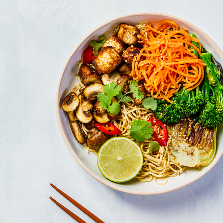 Vegetarian noodles with tofu, broccoli, mushrooms, carrot, bok choy on white stone table. Top view, flat lay, copyspace