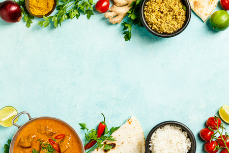 Traditional curry and ingredients on blue background. Curry, lime, ginger, chili, naan bread, rice, couscous, herbs and spices Flat lay