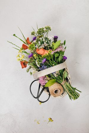 Bouquet of wild flowers in a basket. Flat lay, top view