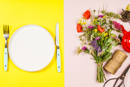 Flat lay of Wild flower bouquet and white plate on pastel color background Stock Photo