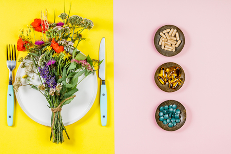Flat lay of wild flower bouquet on white plate and herbal capsules. Clean eating, paleo, biohacking, herbal medicine concept 版權商用圖片