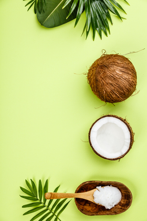 Coconut oil, tropical leaves and fresh coconuts Standard-Bild - 105457862