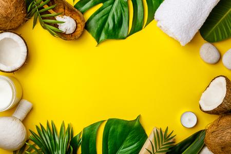 Aceite de coco, hojas tropicales y cocos frescos.