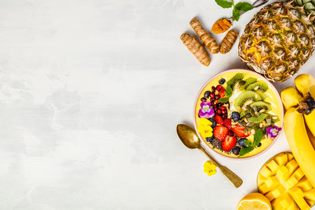 Mango banana pineapple turmeric breakfast superfoods smoothie bowl topped with fruits, berries and seeds. Overhead top view flat lay
