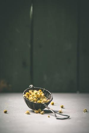 chamomile tea in strainer on vintage background Banco de Imagens