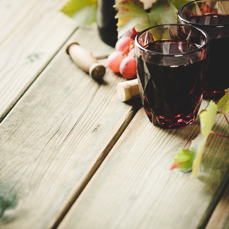 Red wine composition. Red wine glasses, bottle of wine, grapes and leaves on rustic background. Space for text