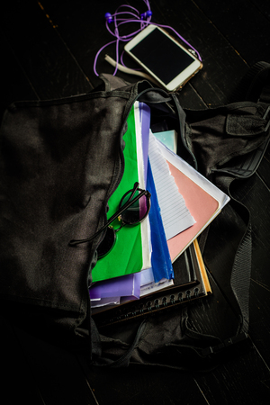 Opened schoolbag with lunch and smartphone on the wooden floor Banco de Imagens