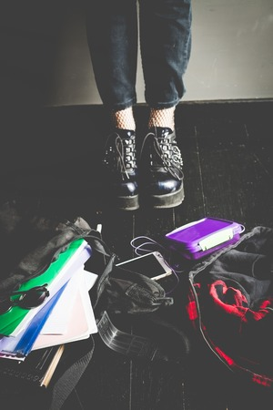 Young alternative girl on the black floor with a school bag