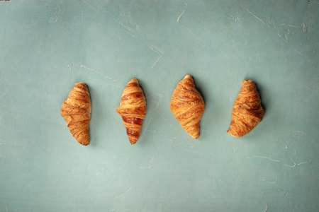 Fresh Croissants on blue background, flat lay