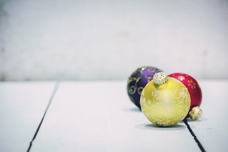 Various christmas tree baubles on wooden background