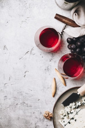 Glasses of red wine, cheese and grapes on rustic concrete backgr Stock Photo