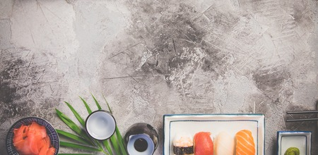 Flat-lay of sushi set on grey concrete background, horizontal composition
