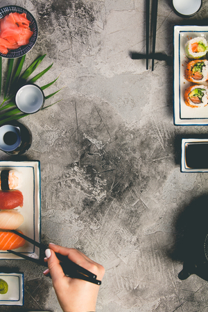 Flat-lay of sushi set on grey concrete background, vertical composition Stock Photo