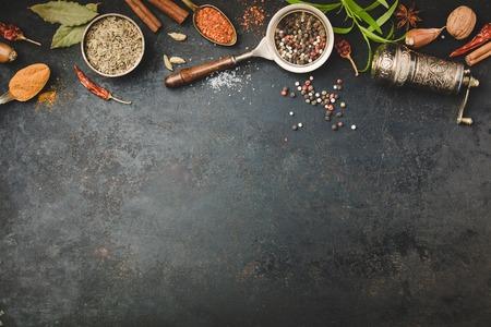 Spices and vintage pepper grinder on dark background