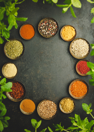 Circle frame composition of spices and herbs over dark background - flat lay Фото со стока