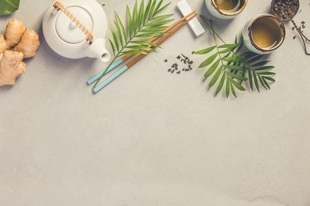 Tło azjatyckie jedzenie, herbata i pałeczki na szarym tle betonu. Zdjęcie Seryjne