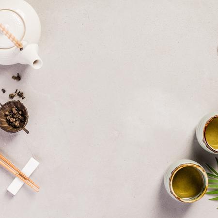 Fond de cuisine asiatique - thé et baguettes sur fond de béton gris. Vue de dessus, mise à plat