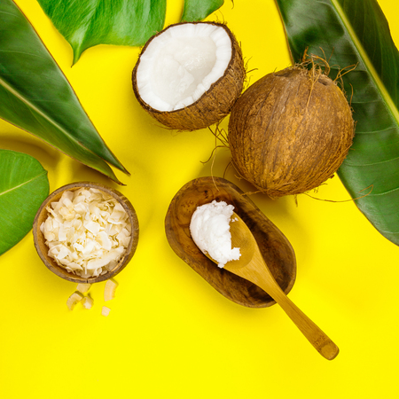 Coconut oil, tropical leaves and fresh coconuts on yellow background, flat lay 版權商用圖片