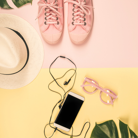 Pair of pink canvas sneakers, smart phone, hat, monstera leaves, headphones and glasses on pink background, top view, flat lay. Trendy fashion woman accessories. Lifestyle or travel concept