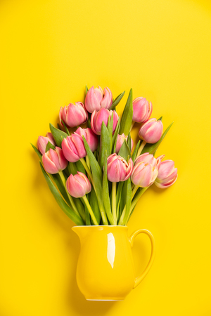 This feminine, floral stock photograph features pretty Fresh pink tulips in a jug on yellow