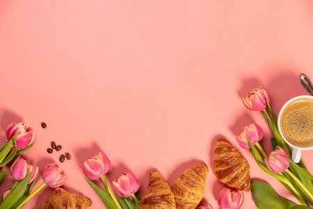 Morning coffee, croissants and a beautiful flowers on pink Stock Photo