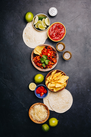 Concept of Mexican food corn tortillas, nachos, salsa, avocado, limes, cheese, chili con carne flat lay Banco de Imagens