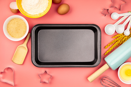 Baking ingredients and empty baking tray on pink