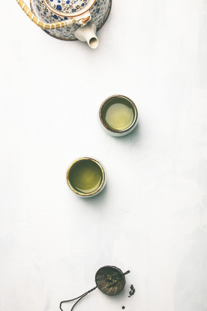 Tea composition, green tea on grey concrete background, flat lay