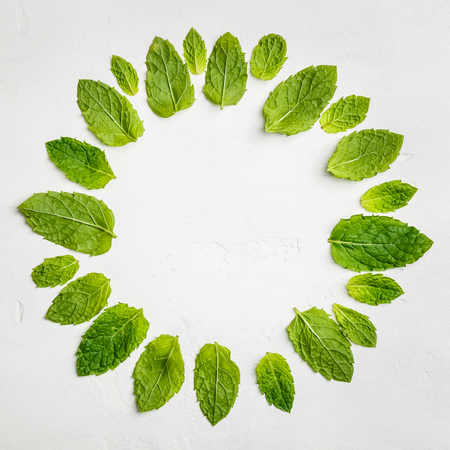 Mint leaves composition on white stone background, flat lay Imagens