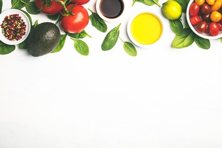 Olive oil, vinegar, vegetables and spices on white stone background. Making salad, cooking, clean eating, dieting concept. Flat lay