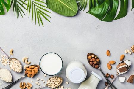 Lait végétalien et ingrédients sur fond de béton gris, mise à plat. Concept d'alimentation végétalienne, végétarienne et propre Banque d'images
