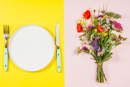 Flat lay of Wild flower bouquet and white plate on pastel color 스톡 콘텐츠